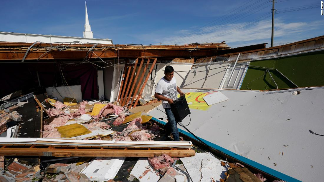 Benjamin Luna helps recover items from the children's wing of the First Pentecostal Church in Orange, Texas, in agosto 27.