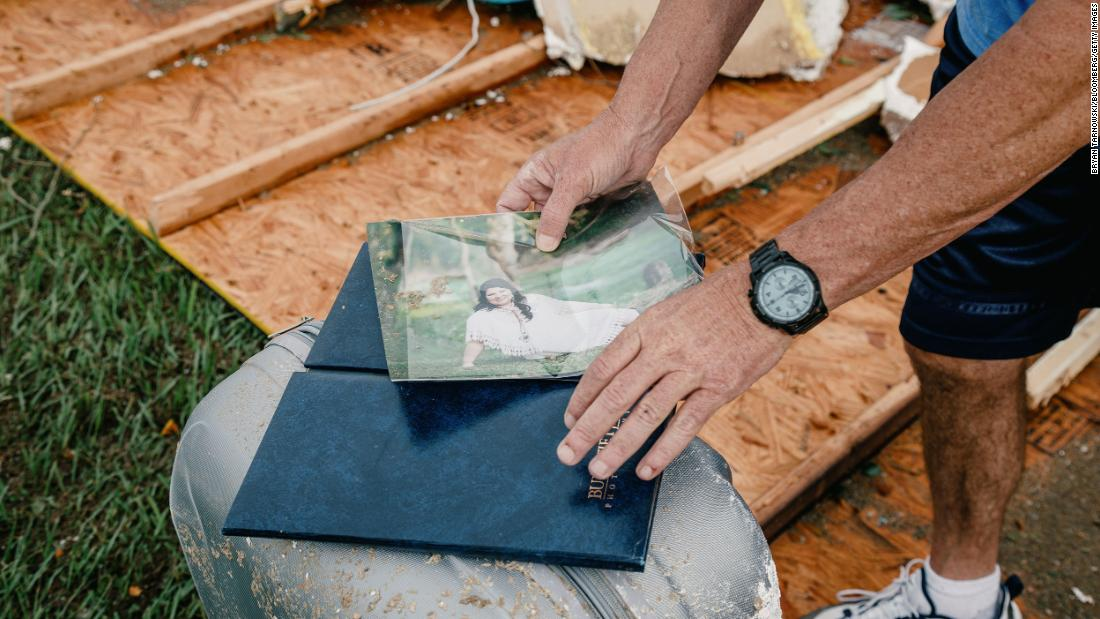 A person holds a photo taken from a damaged home in Cameron Parish, 路易斯安那州, on August 27.