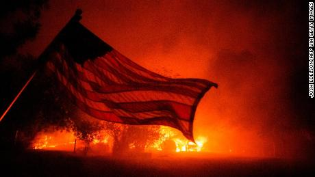 An American flag blows in the wind in front of a burning home in Vacaville, California, during the LNU Lightning Complex fire on August 19, 2020.