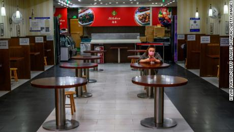 A Chinese woman wears a protective mask as she sits in a nearly empty restaurant at a shopping mall on March 26 during coronavirus restrictions in Beijing, China.