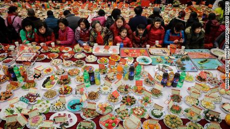 Neighborhood residents sit around a table full of homemade dishes on February 9, 2018 in Wuhan, Hubei province, China, to celebrate the Lunar New Year.