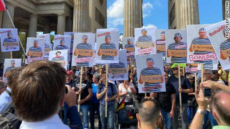 """Some held up signs showing pictures of German lawmakers and the word """"guilty."""""""