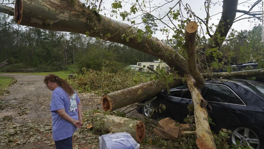 A person stands in front of a damaged vehicle near Orange, Texas, in agosto 28.