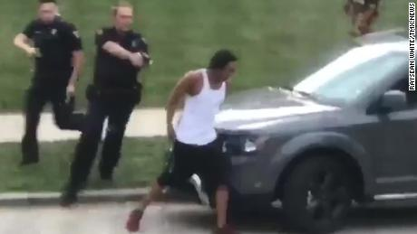 In this screengrab taken from video, police follow Jacob Blake as he walks to the driver's side door of an SUV on August 23. He was shot moments later.