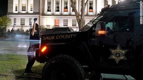 A protester obstructs an armored vehicle attempting to clear the park of demonstrators during clashes outside the Kenosha County Courthouse on August 25.