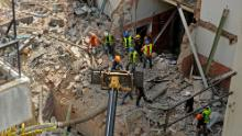 Rescue workers dig through the ruins of a badly damaged building on September 4.