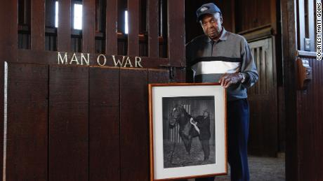 Tom Harbut, son of Man O' War's legendary groom Will Harbut, poses in 2010 with a vintage photograph of his father grooming the great sire by the stall where it was stabled.