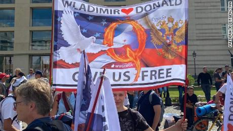 "Marchers held signs that implored US President Donald Trump and Russian President Vladimir Putin to ""free"" Germany."