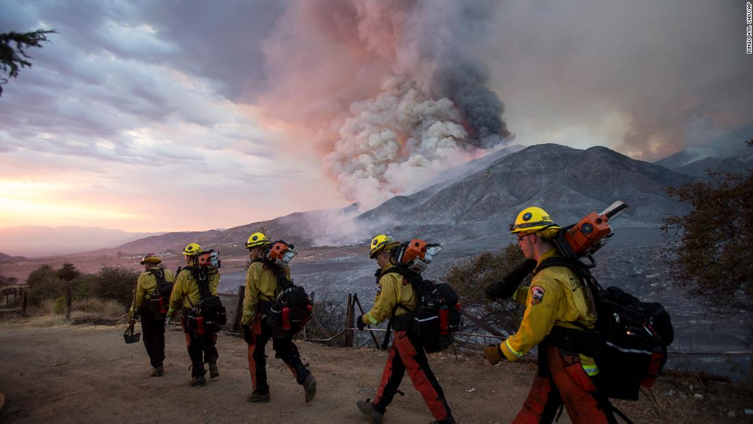 Firefighters walk in a line in Yucaipa on September 5.