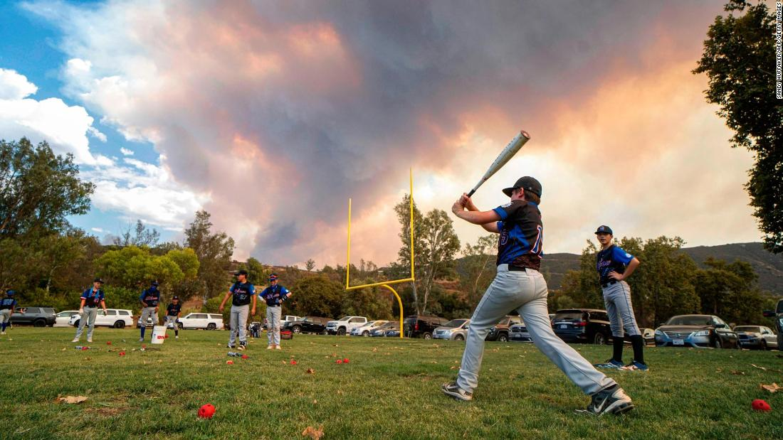 Little League baseball players warm up for a game near Dehesa, 캘리포니아, as the Valley Fire burns on September 6.