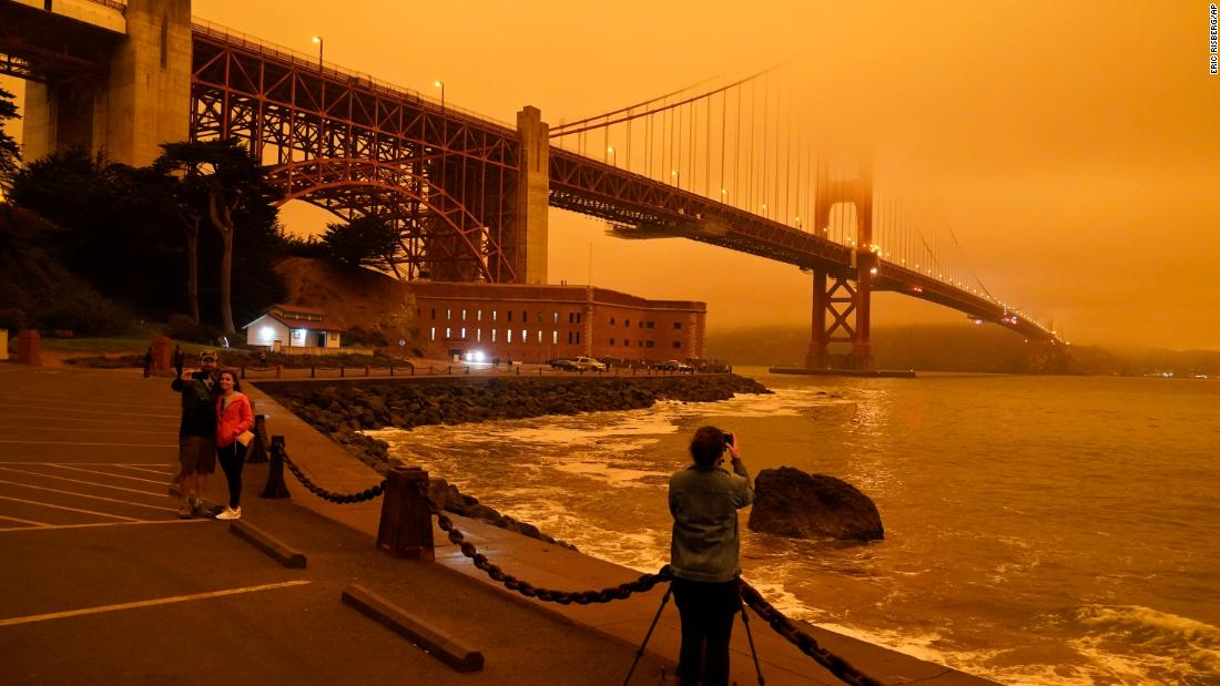 People stop to take pictures of the Golden Gate Bridge as it is affected from smoke by nearby wildfires on September 9.