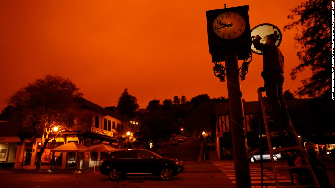 Bejhan Razi, a senior building inspector in Mill Valley, 캘리포니아, checks out repairs on a lamp-post clock as the sky is illuminated by nearby wildfires.
