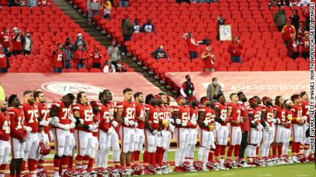 Members of the Kansas City Chiefs lock arms before taking to the field.