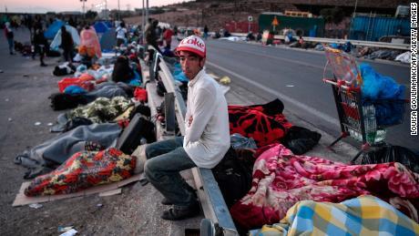 ชายคนหนึ่งนั่งบนกำแพงกั้นขณะที่ผู้อพยพเร่ร่อนและผู้ลี้ภัยนอนหลับอยู่ริมถนนตามเปลวไฟ