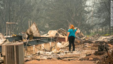 A woman surveys the damage to a home owned by her son in a mobile home park on September 11, 2020 in Ashland, 俄勒冈州.