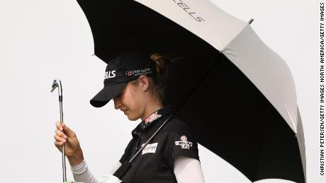 Nelly Korda of the United States takes shelter from the sun as she selects a club from her bag during her third round at Mission Hills.