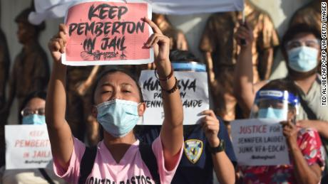 People hold placards protesting against the decision to pardon Pemberton at a demonstration in Manila, Philippines on September 8, 2020.