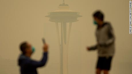 Smoke obscures the Space Needle as people take photos in Seattle's Kerry Park on Saturday.