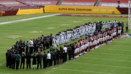 The Washington Football Team and the Philadelphia Eagles stand together on the field before the game at FedExField in Landover, Maryland, on Sunday, September 13.