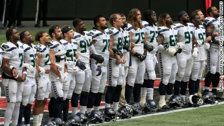 """The Seattle Seahawks line up in the end zone as """"Lift Every Voice and Sing"""" is played before their game against the Atlanta Falcons at Mercedes-Benz Stadium in Atlanta, Georgia, on Sunday."""