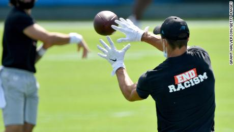 Carolina Panthers players wear End Racism shirts as they warm up before a game against the Las Vegas Raiders on September 13, 2020 in Charlotte, North Carolina.