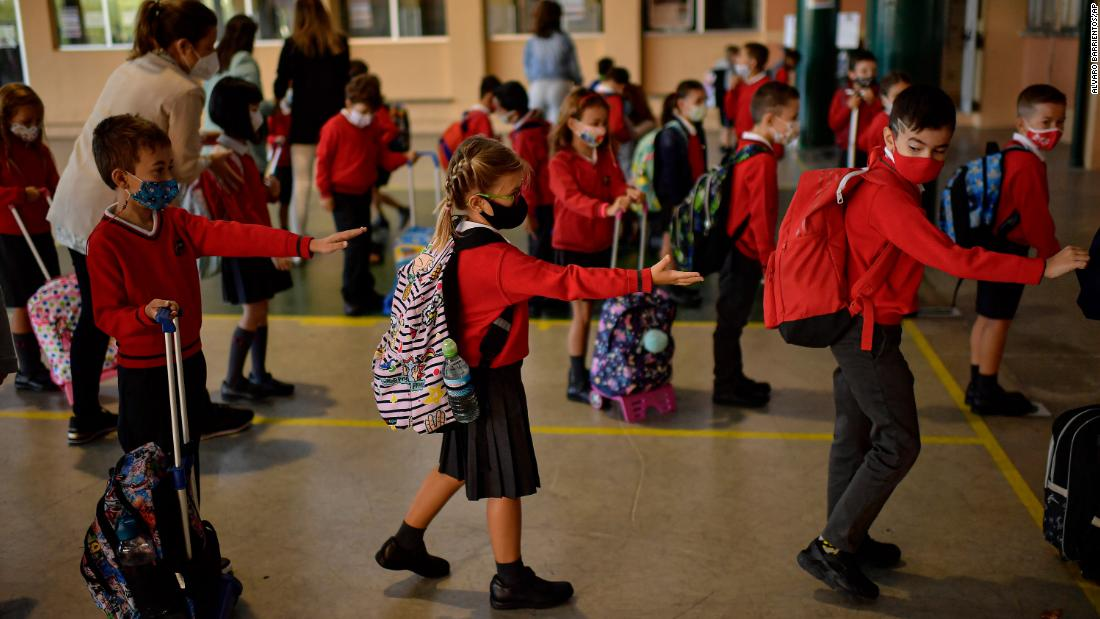 Young students make sure they are spread out from one another as they stand in a line before entering a classroom in Pamplona, Spagna, a settembre 7.