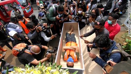 A man caught not wearing a face mask in public lies in a mock coffin while members of the public and the media take pictures as part of punishment by local authorities and enforced by local police in Jakarta on September 3.