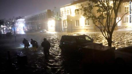 People walk on flooded streets in search of their vehicle early Wednesday in Pensacola, Florida.
