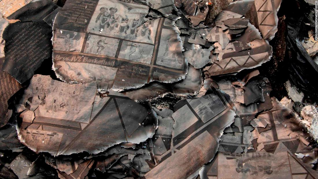 A charred yearbook lies in the debris as Fred Skaff and his son Thomas clean up their home in Phoenix, 오레곤, 9 월 16.