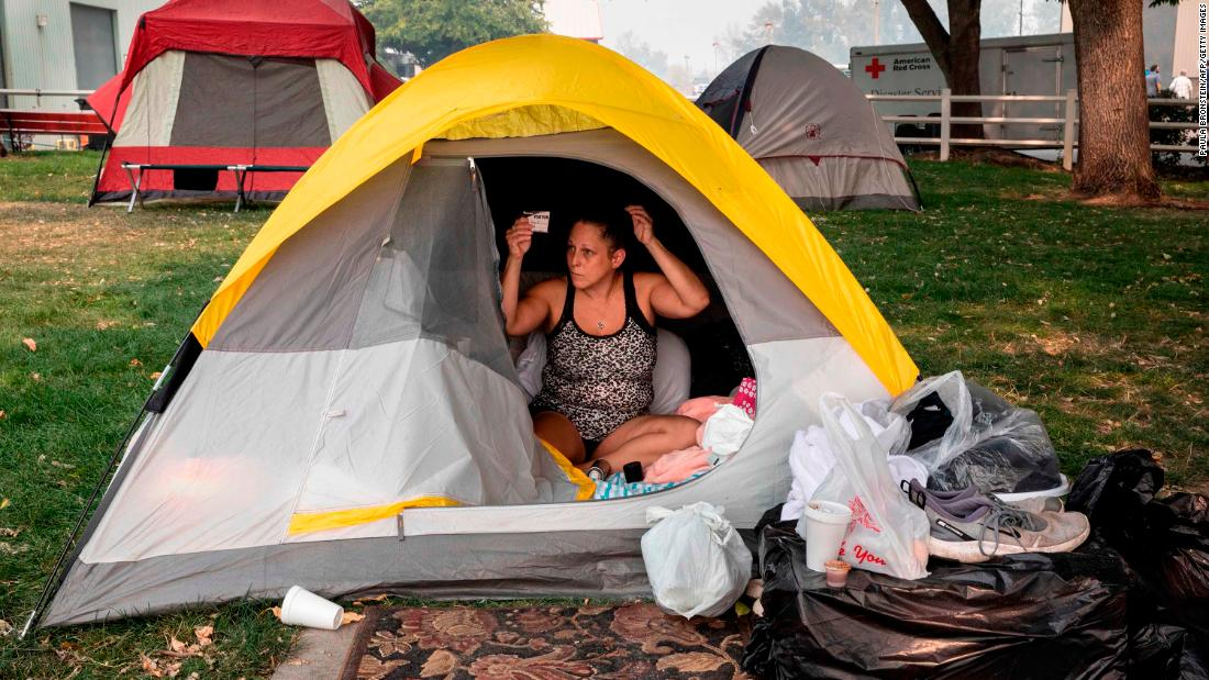 Stacey Kahny fixes her hair inside her tent at the evacuation center at the Jackson County Fairgrounds in Central Point, Oregon, 9 월 16. Kahny lived with her parents at a trailer park in Phoenix, Oregon,오레곤was destroyed by fire.