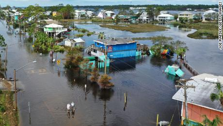 An aerial view from a drone shows people walking through a flooded street in Gulf Shores, Alabama.