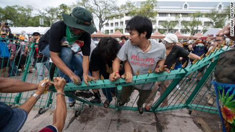 Pro-democracy protesters push over a fence surrounding the  Sanam Luang field during a protest in Bangkok, Thailand, on September 19.
