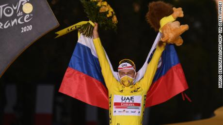 Slovenia's Tadej Pogacar wearing the overall leader's yellow jersey celebrates on the podium after winning the 107th edition of the Tour de France cycling race.