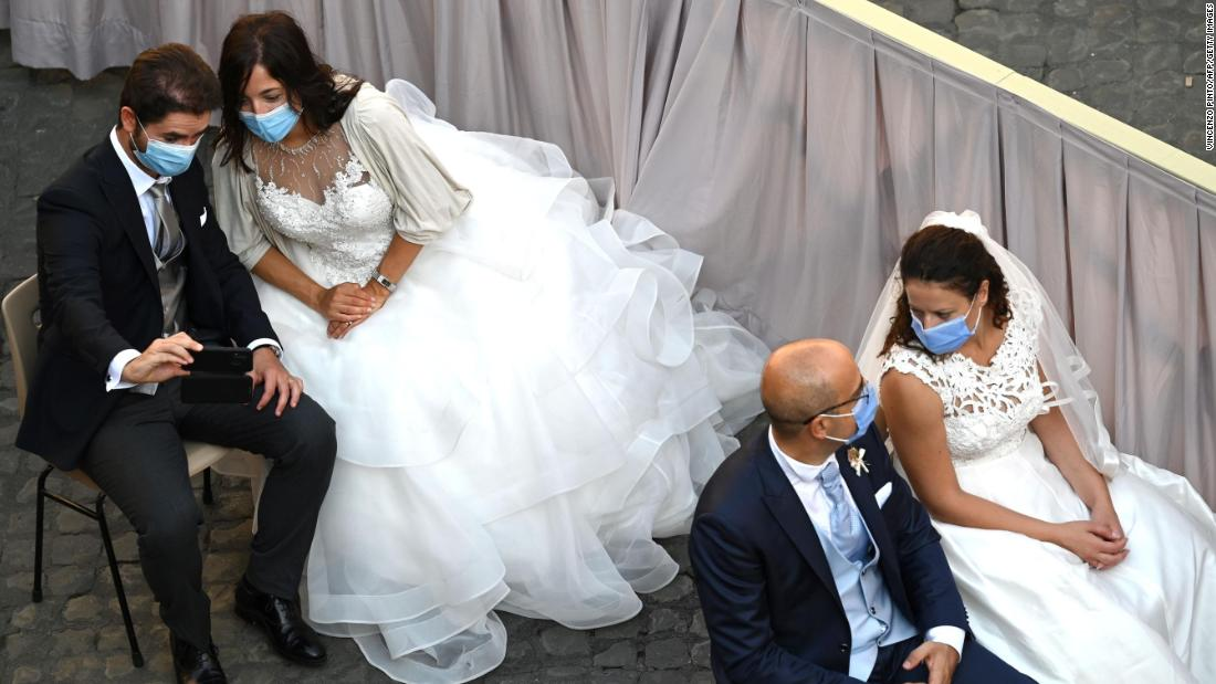 Brides and grooms wait for the Pope's arrival at the San Damaso courtyard in the Vatican on September 16.