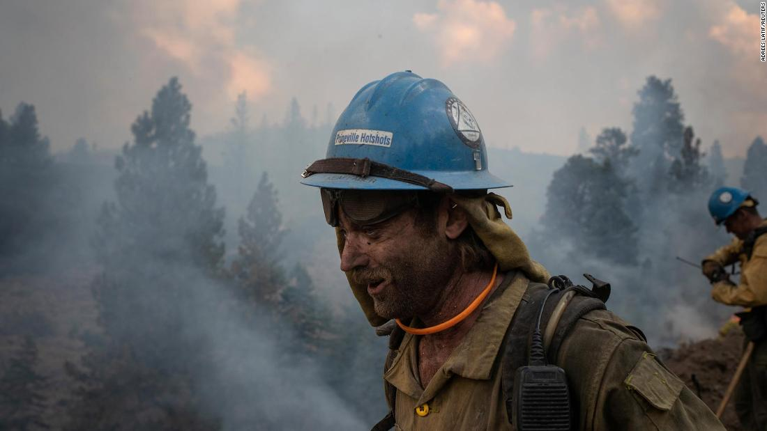 Firefighter Kirk McDusky walks past smoke rising from the Brattain Fire in Paisley, Oregon, on September 18.
