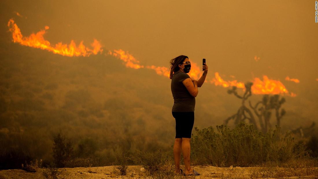 A woman takes photos as the Bobcat Fire burns in Juniper Hills, 캘리포니아, 9 월 18.