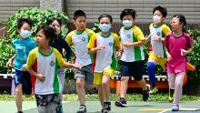Students wearing face masks run during a sports class at Dajia Elementary School in Taipei on April 29, 2020.
