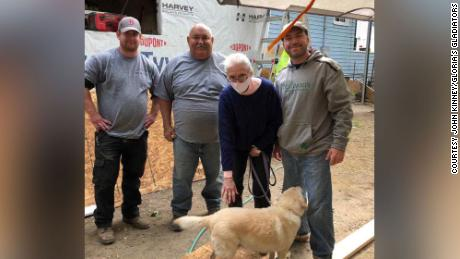 "Gloria Scott is surrounded by members of the ""Gloria's Gladiators"" team that is rebuilding her home."