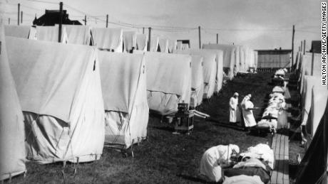 1918: Nurses care for victims of an influenza epidemic outdoors amid canvas tents in Lawrence, Massachusetts.