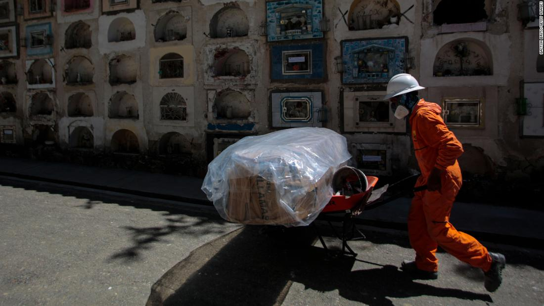 A cemetery worker in La Paz, Bolivia, pushes a cart with a plastic-wrapped coffin on September 23.