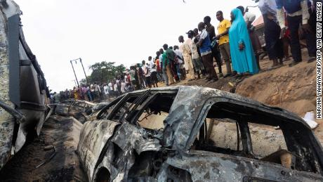 Bystanders look on at the wreckage of a truck that caught fire in Lokoja, Nigeria, on September 23, 2020. - At least nine people, including several students, were killed when a truck carrying petrol overturned and caught fire on a busy road in central Nigeria on Wednesday. The accident happened at Lokoja, the capital of Kogi state, after the truck's brakes failed and its driver lost control. (Photo by Haruna Yahaya / AFP) (Photo by HARUNA YAHAYA/AFP via Getty Images)