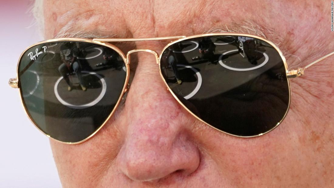 People sitting in social-distancing circles are reflected in Biden's sunglasses as he speaks in Charlotte, North Carolina.