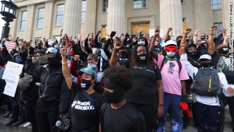 Demonstrators raise their fists as they gather on the steps of the Louisville Metro Hall on September 24, 2020.