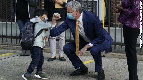 New York City Mayor Bill de Blasio does a welcome elbow bump with a pre-K student in Queens. The mayor has pushed for schools to resume in-person tuition.
