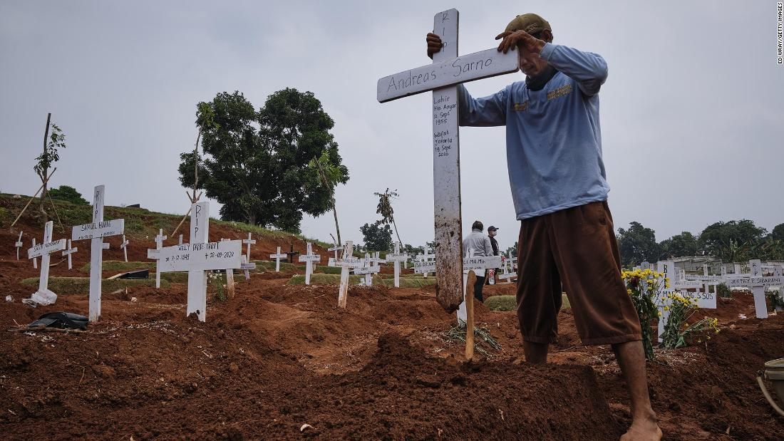 A grave digger in Jakarta, Indonesia, plants a cross in a public cemetery, part of which is reserved for suspected Covid-19 victims, a settembre 26.