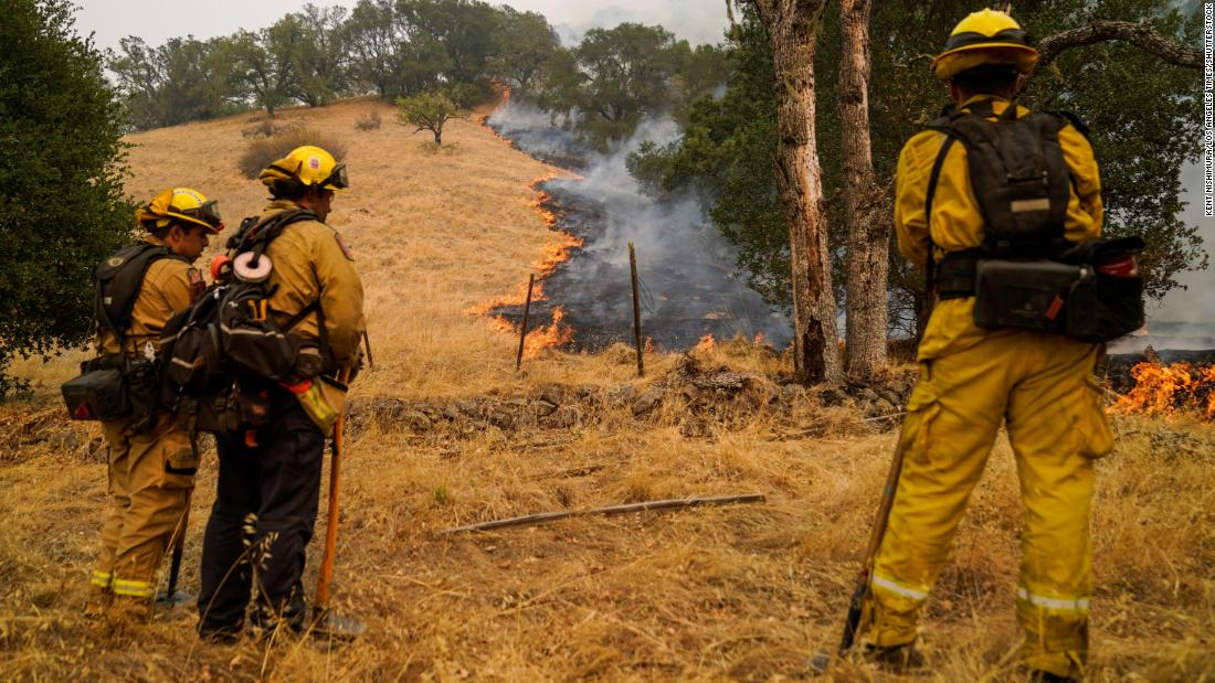 Firefighters watch the Glass Fire slowly creep across a clearing near Calistoga on September 29.