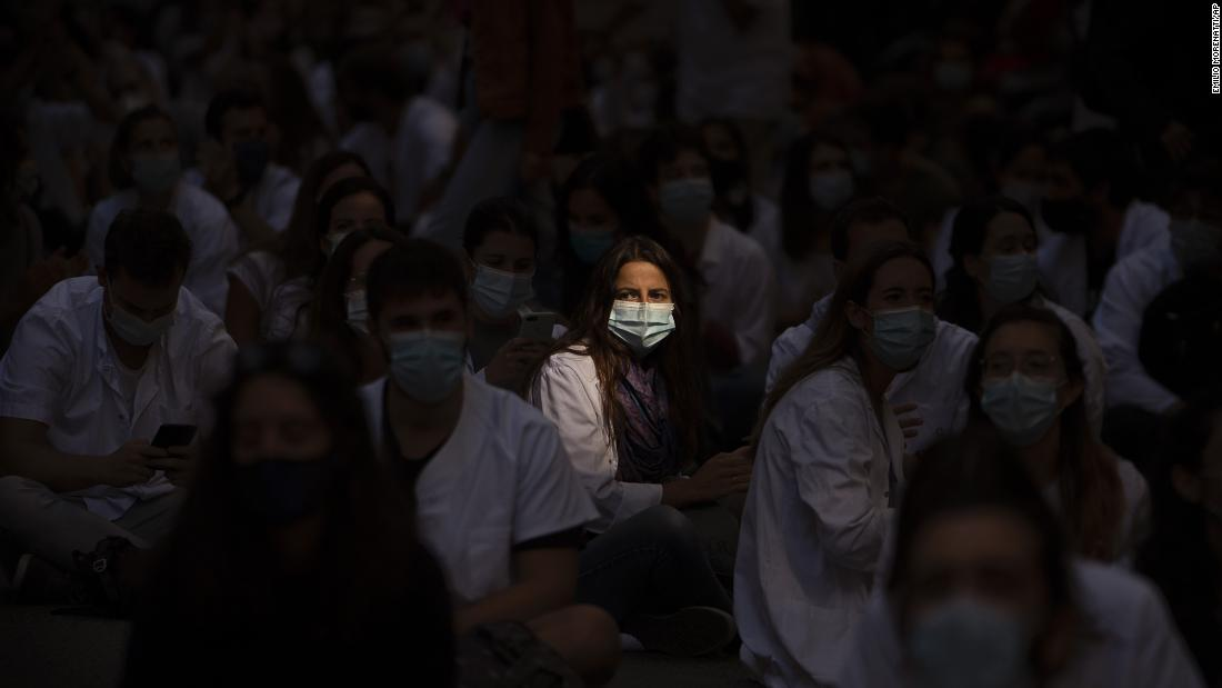 Medical residents sit in the middle of a street as they protest their working conditions in Barcelona, Spagna, a settembre 28.