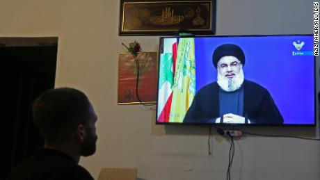 A man watches Lebanon's Hezbollah leader Sayyed Hassan Nasrallah speaking on television, inside a shop in Houla, southern Lebanon on September 29, 2020.