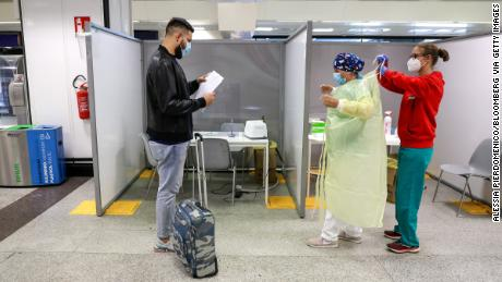 A passenger waits to undergo a swab test at a Covid-19 rapid test facility at Fiumicino Airport in Rome, 九月 25.