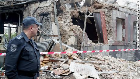 شیل فائر سے تباہ شدہ ایک عمارت کے سامنے ایک پولیس اہلکار کھڑا ہے۔